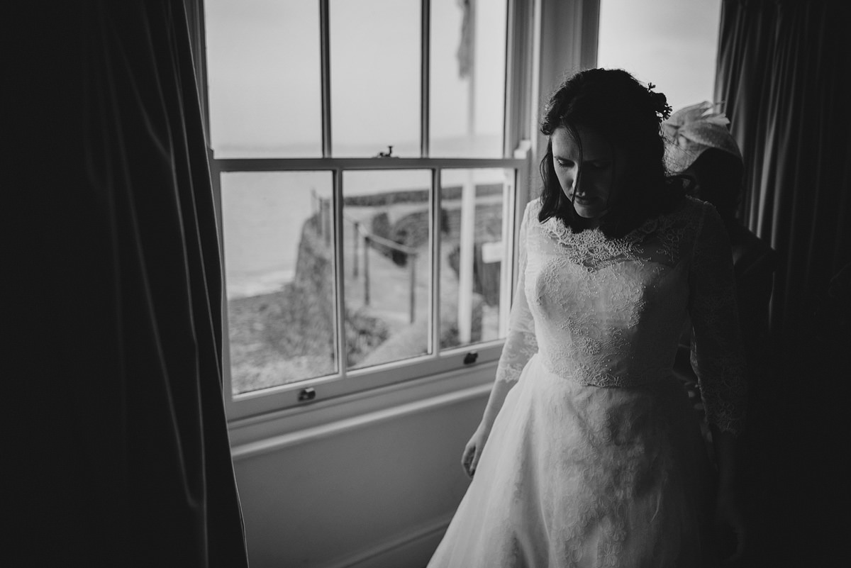 Bride putting on dress at Red Lion Hotel in Clovelly