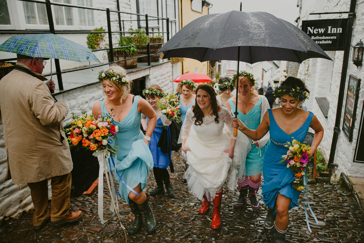 Bride and bridesmaids walking through Clovelly