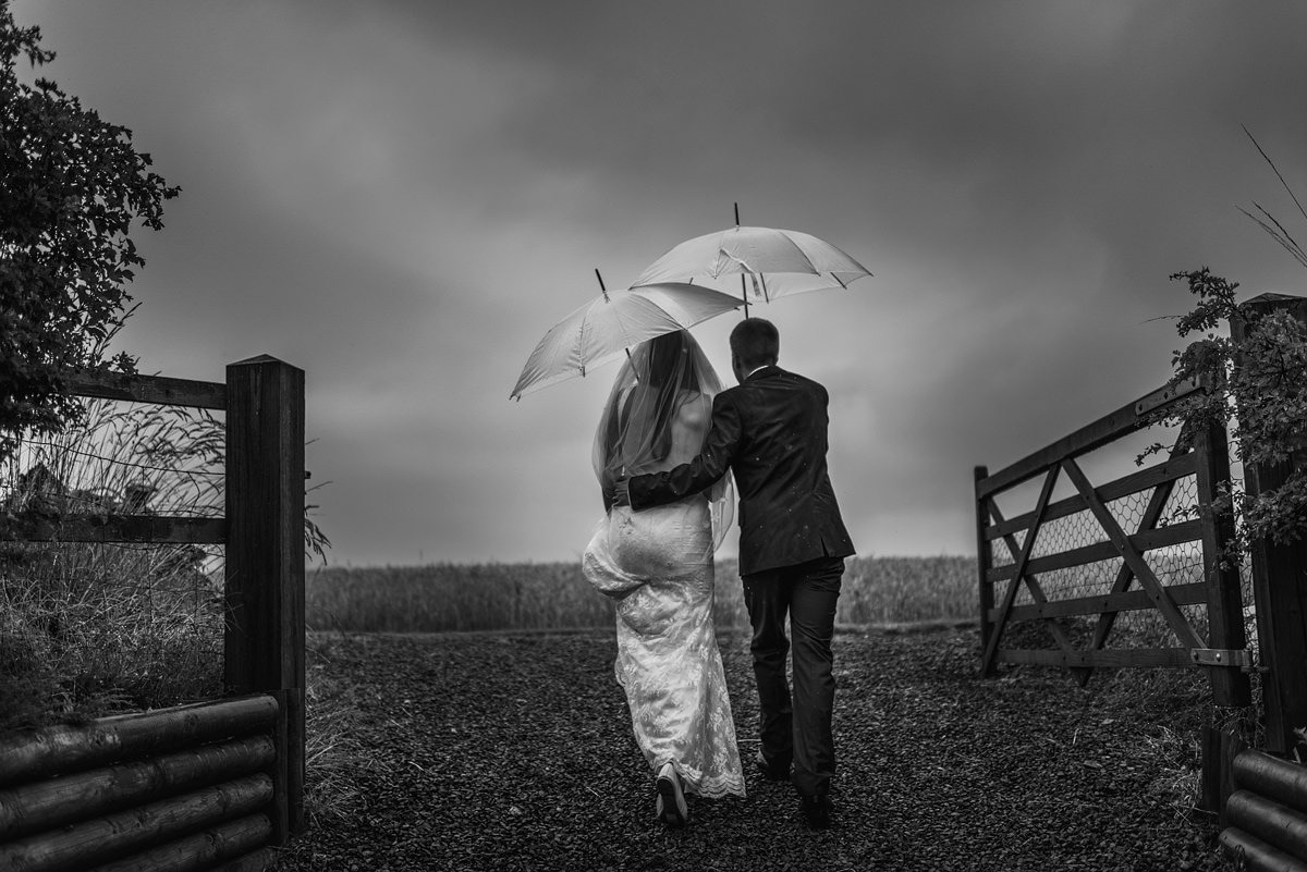 Wedding photo in rain with umbrella in Shropshire