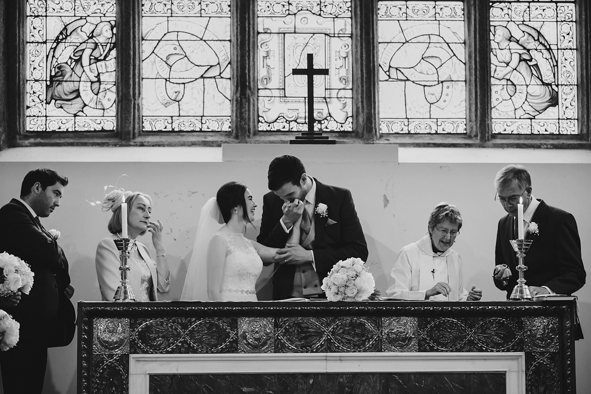Groom kissing bride's hand after ceremony