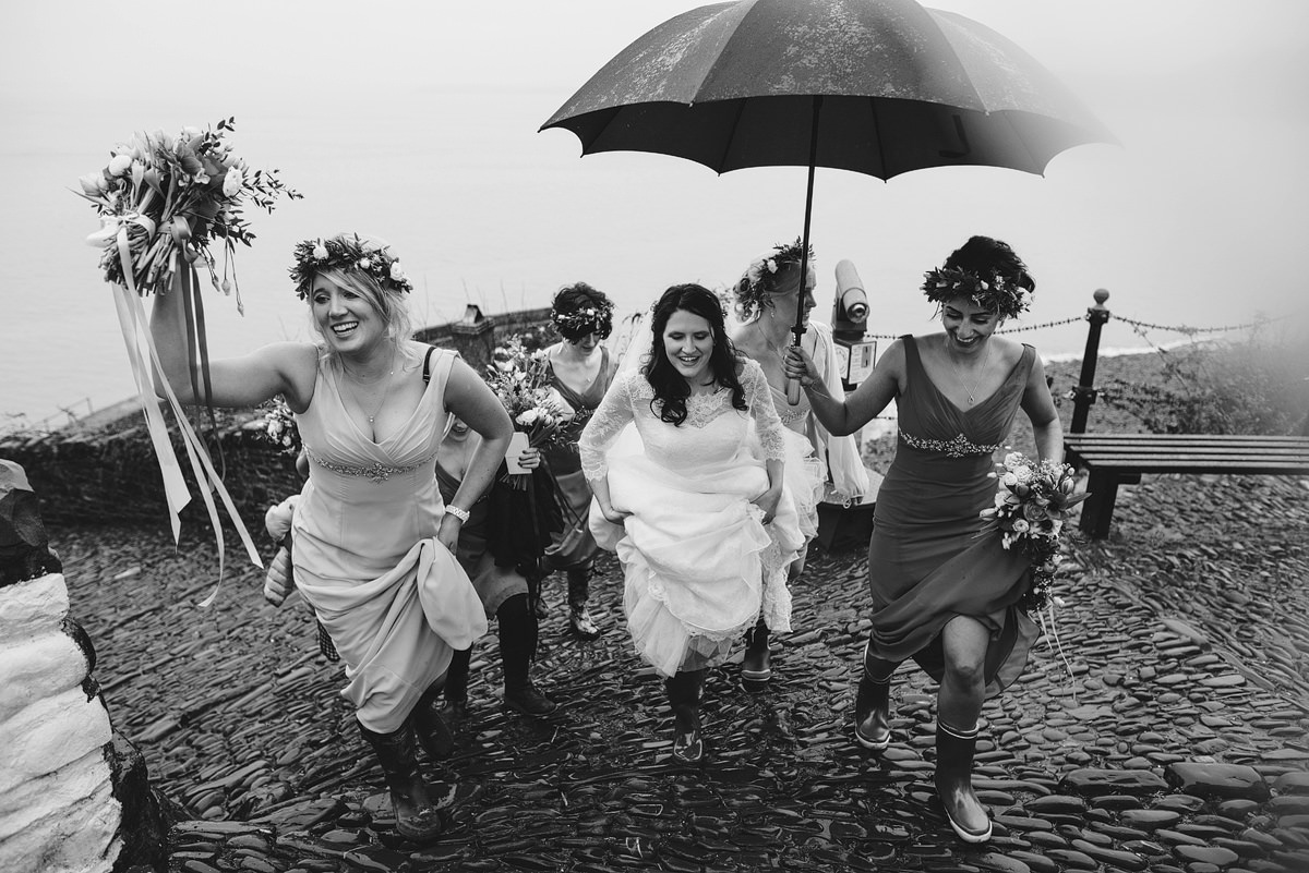 Bride and bridesmaids in Clovelly with umbrellas