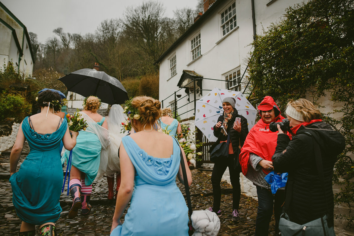 Wedding party walking through Clovelly, North Devon