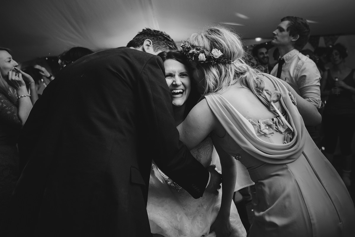 Bride embracing friends at a wedding in Croyde
