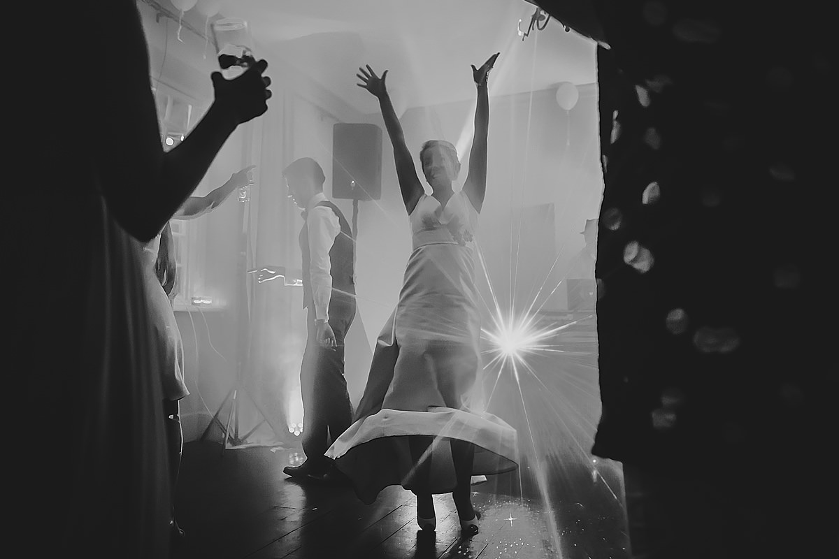 Bride arms up in the air on dance floor
