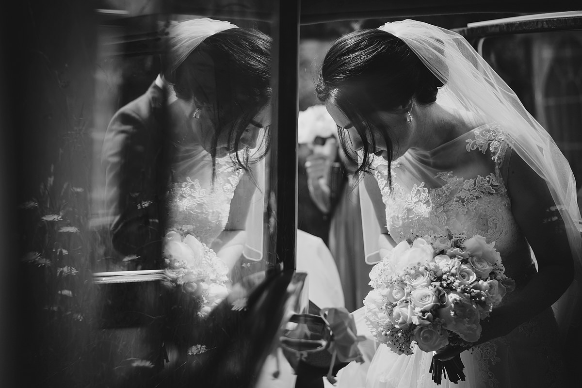 Bride's reflection in wedding car