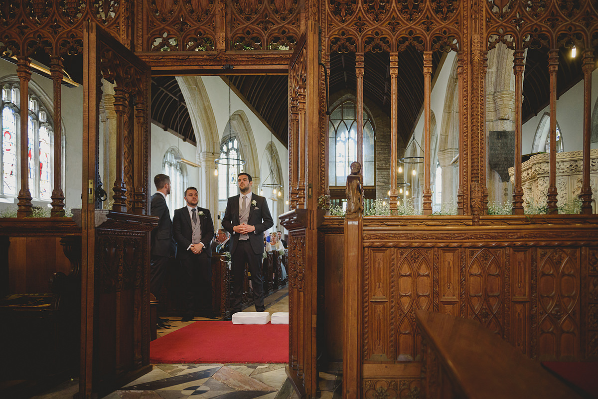 Groom waiting at All Saints Church in Holbeton