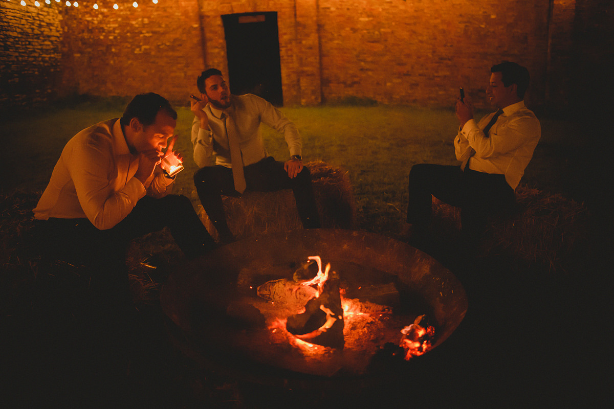 Guests smoking cigars by open fire
