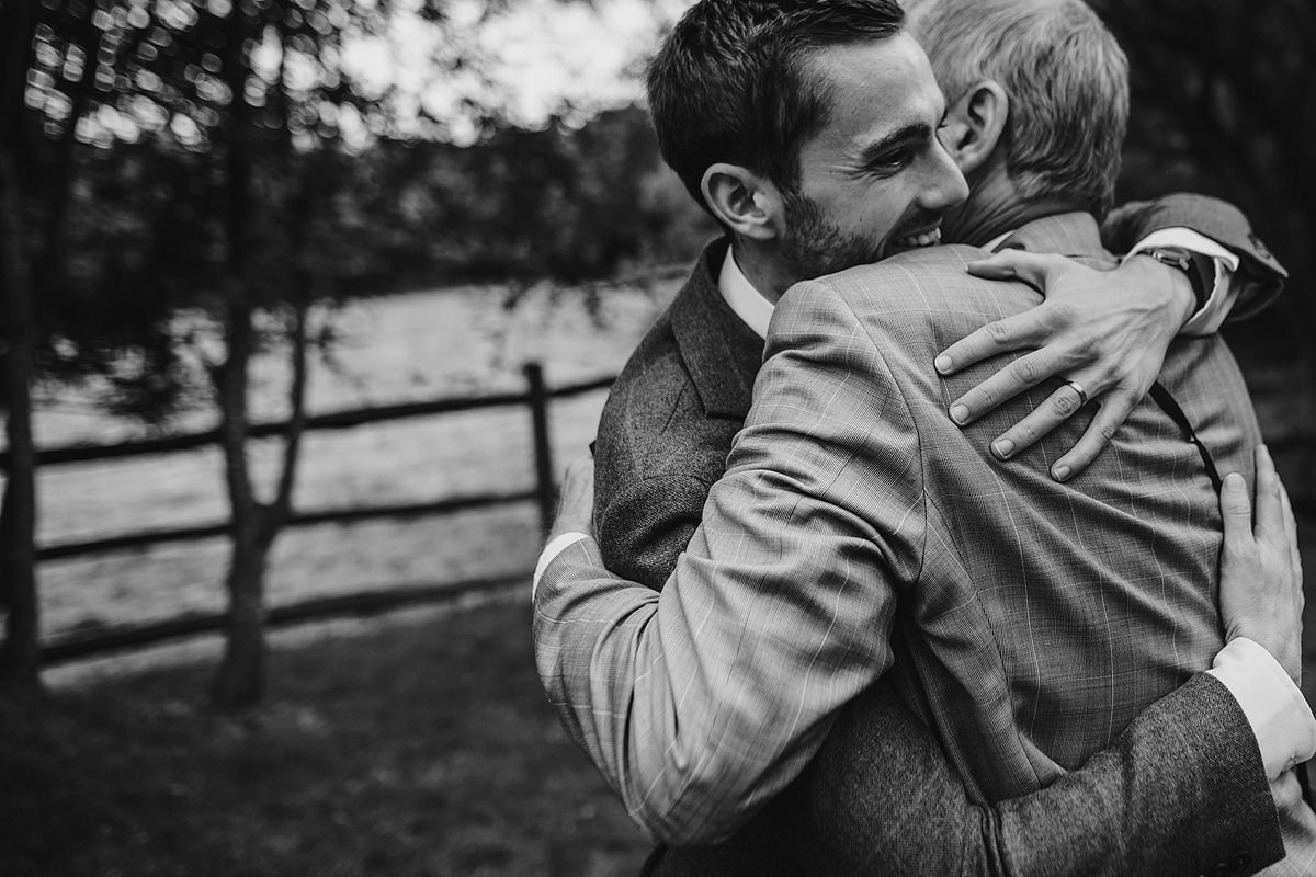Emotional groom hugging dad