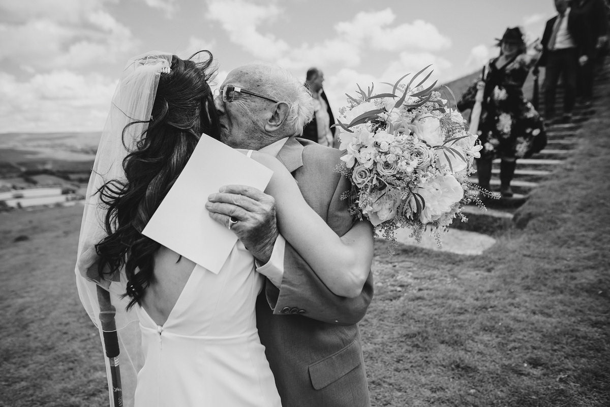 Emotional grandad hugging bride