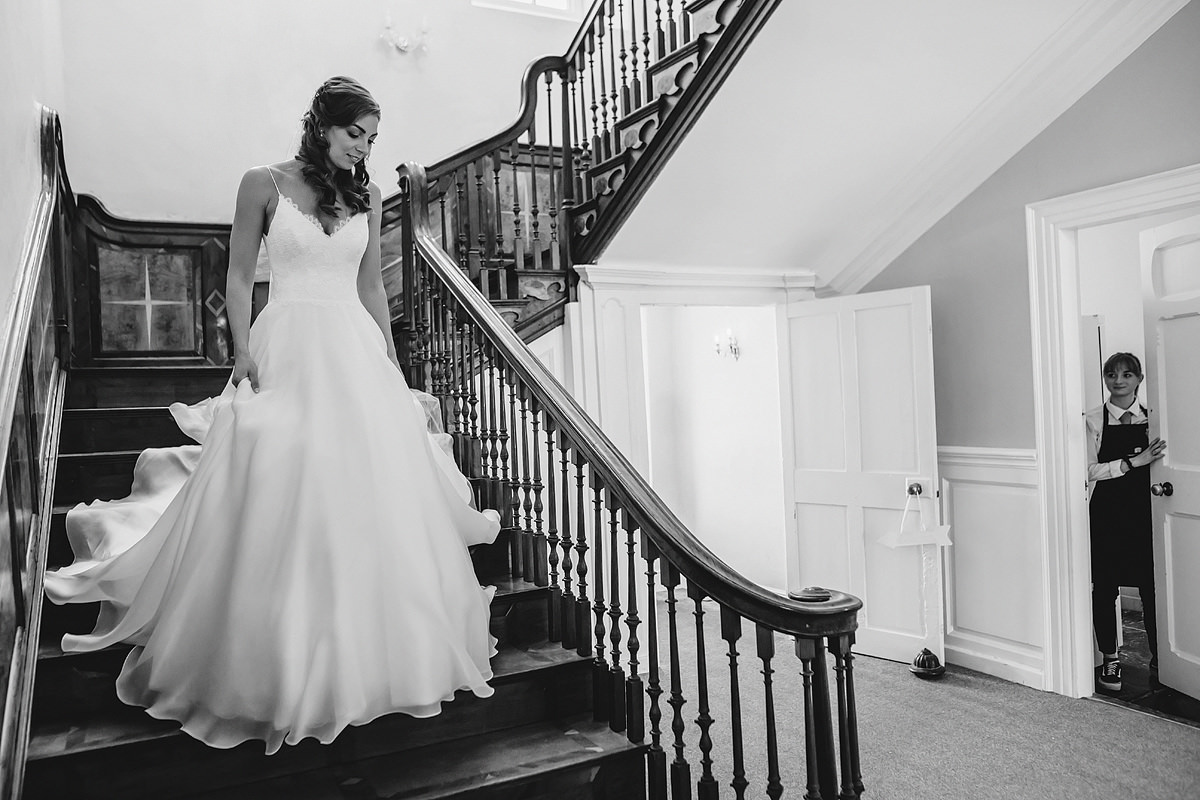Bride walking down stairs in wedding dress