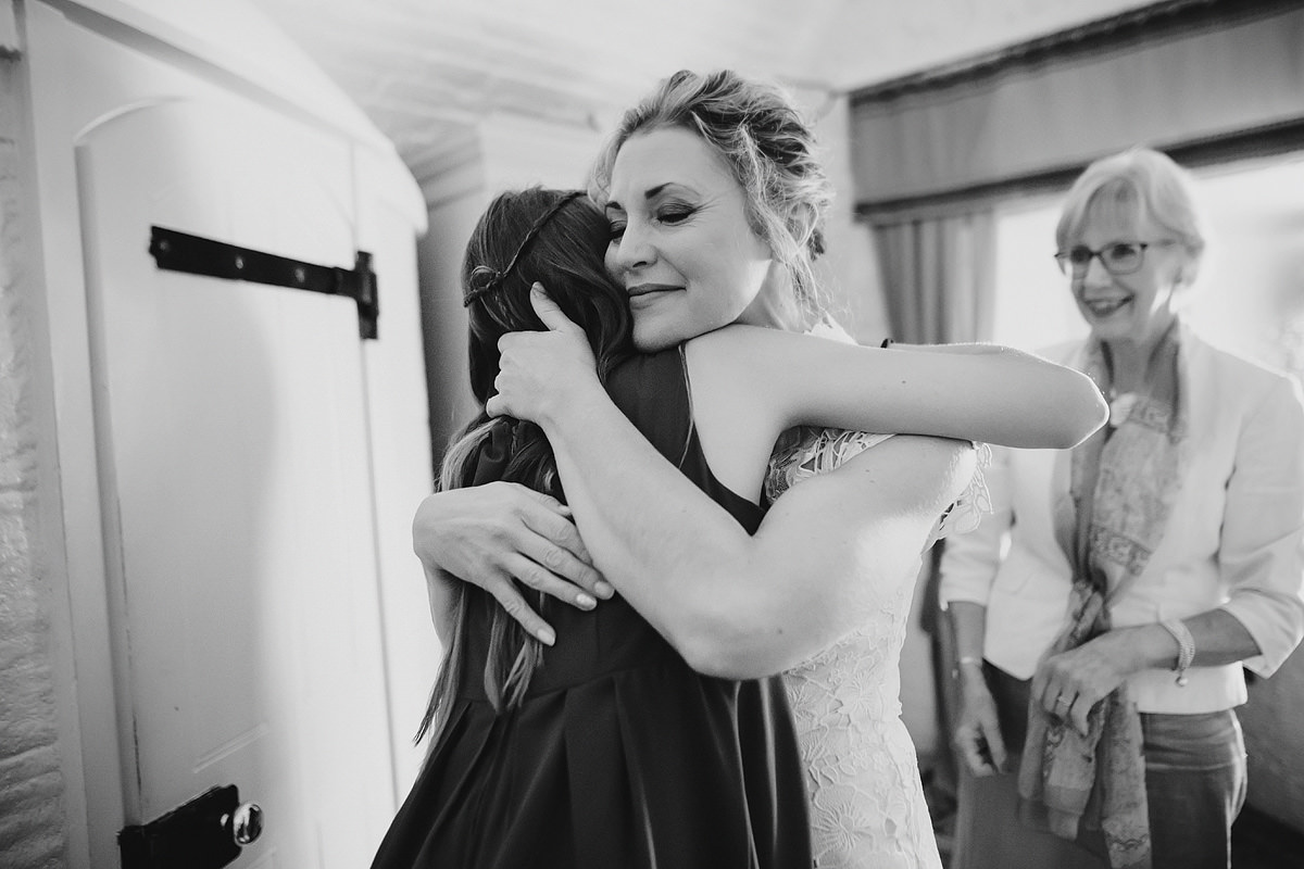 Emotional bride hugging daughter